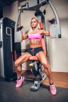 Plakat atrakcyjna kobieta w siłowni na maszynie do ćwiczeń