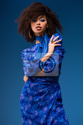 Plakat attractive african american woman in dress looking at camera isolated on blue
