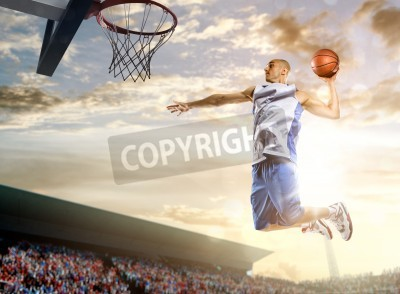 Plakat Basketball player in action on background of sky and crowd