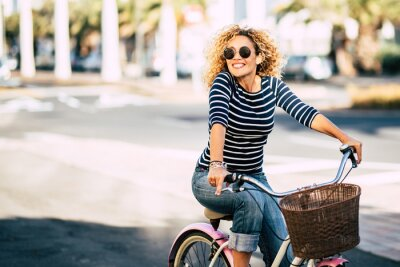 Plakat Beautiful and cheerful adult young woman enjoy bike ride in sunny urban outdoor leisure activity in the city - happy people portrait - trendy female outside having fun