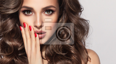 Plakat Beautiful model with long curly hair . Fashion trend image , the girl with red manicure on nails. Cosmetics ,makeup and wavy hairstyle