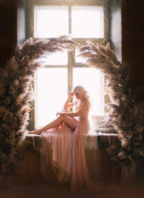 Plakat Beautiful sad woman sitting on vintage windowsill retro window. Sexy bare leg. Beige evening peach pink nude dress Princess blond long wavy hair pearl Tiara. Backdrop cane natural arch decor dark room