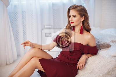 Plakat Beautiful sexy woman in maroon dress posing near Christmas Tree. Attractive and sexy smiling blond girl wait for Christmas night.Young beautiful woman on Christmas Eve alone in her apartment