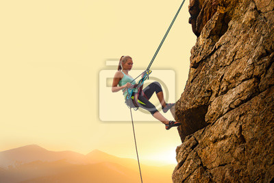 Plakat Beautiful Woman Climbing on the Rock at Foggy Sunset in the Mountains. Adventure and Extreme Sport Concept