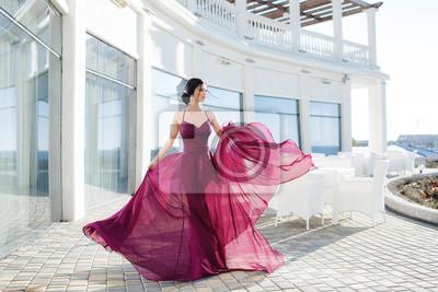 Plakat Beautiful woman in elegant evening dress. Beautiful young woman, model, in an evening dress outdoors.A portrait of a beautiful elegant woman in the evening dress. Fashion, evening dresses for events.
