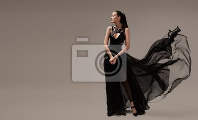 Plakat Beautiful woman in luxury evening black dress. Gray background.