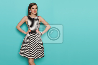 Plakat Beautiful Young Woman In Black And White Striped Dress Is Looking Away