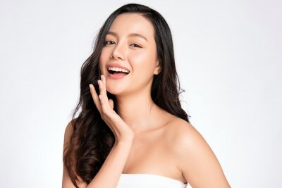 Plakat Beauty face. Smiling asian woman touching healthy skin portrait. Beautiful happy girl model with fresh glowing hydrated facial skin and natural makeup on white background,