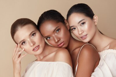 Plakat Beauty. Group Of Diversity Models Portrait. Multi-Ethnic Women With Different Skin Types Posing On Beige Background. Tender Multicultural Girls Standing Together And Looking At Camera.