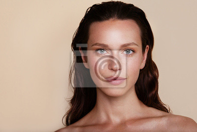 Plakat Beauty woman portrait. Beautiful spa model girl with perfect fresh clean skin. Youth and skin care concept. Beige background. Nude makeup
