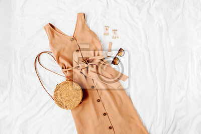 Plakat Beige dress with bamboo bag and accessories on white bed. Women's stylish autumn or summer outfit. Trendy clothes. Flat lay, top view.