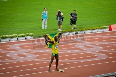 Plakat Beijing - Aug 16: Usain Bolt celebrates holding the Jamaican flag after setting new world 100 meter record  for men