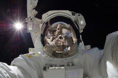 Plakat bliska widok pływających astronautów z odbiciem na wykazywanie stacji kosmicznej (niektóre elementy wykonane przez NASA)