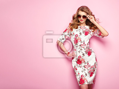 Plakat Blondynki młoda kobieta w kwiecistej wiosny lata sukni. Dziewczyna pozuje na różowym tle. Letni kwiatowy strój. Stylowa falująca fryzura. Fotografia mody. Seksowny dama w stylowe okulary