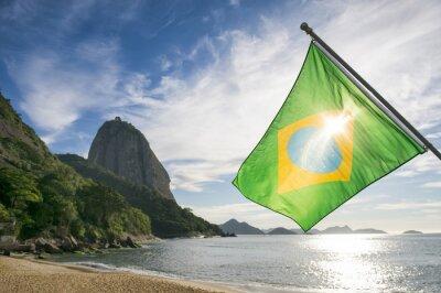Plakat Brazilian flag przy Praia Vermelha Red Beach z widokiem na wschód słońca na Głowę Cukru Pao de Acucar w Rio de Janeiro, Brazylia
