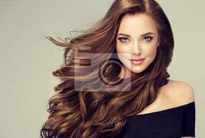 Plakat Brunetka dziewczyna z długimi i błyszczącymi falistymi włosami. Piękny model z kręcone fryzury.