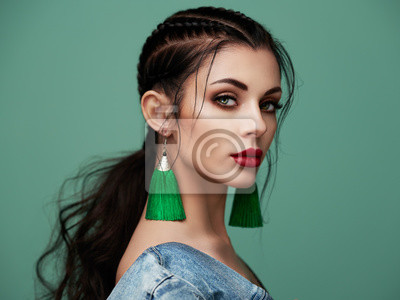 Plakat Brunette girl with perfect makeup. Beautiful model woman with curly hairstyle. Care and beauty hair products. Lady with braided hair. Model with jewelry. Turquoise background