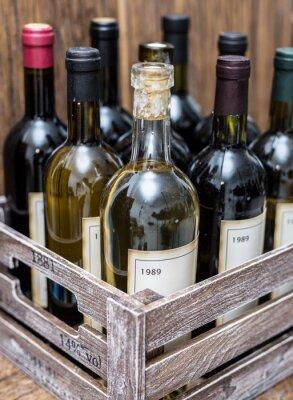 Plakat butelek wina w drewnianej skrzyni.