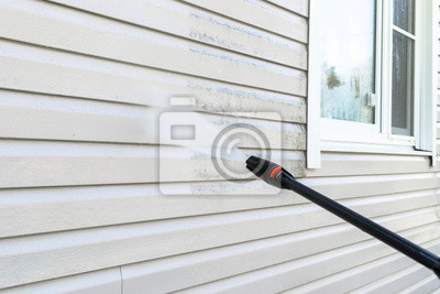 Plakat Cleaning service washing building facade with pressure water. Cleaning dirty wall with high pressure water jet. Power washing the wall. Cleaning the facade of the house. Before and after washing