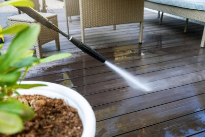 Plakat cleaning wooden terrace planks with high pressure washer