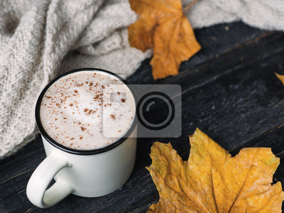 Plakat coffee mug cappuccino with cinnamon on a wooden table with dry autumn leaves and a warm scarf
