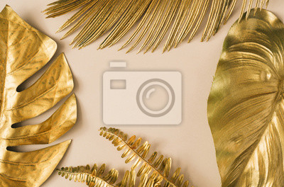 Plakat Creative layout made of golden tropical leaves and palms on beige background. Minimal summer exotic concept with copy space. Border arrangement background.