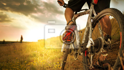 Plakat Cyclist riding the bike down rocky hill at sunset. Close up extreme sport concept