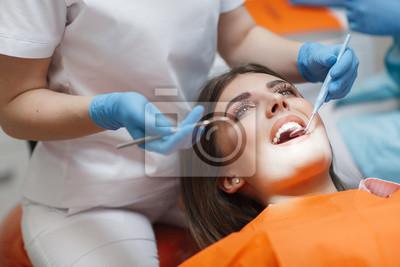 Plakat Dental clinic. Reception, examination of the patient. Teeth care. Young woman undergoes a dental examination by a dentist.Happy patient and dentist concept.Female dentist in dental office talking with