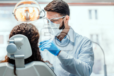 Plakat Dentist working in dental clinic with patient in the chair.