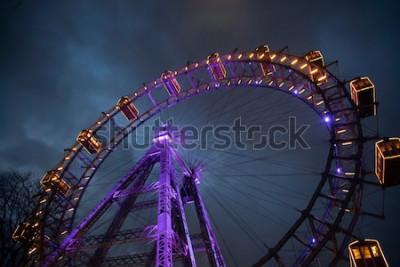 Plakat Diabelski młyn ze światłem między chmurami. Londyńskie oko. Zimowy. Nocne niebo i chmury. Anglia. Wielka Brytania