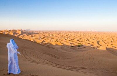 Plakat Dubaj, mężczyzna w tradycyjnym stroju w obszarze desertic Al dhana