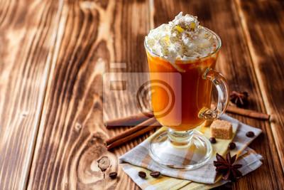 Plakat Dyniowy pikantności latte z batożącą śmietanką i cynamonem w szkle na nieociosanym drewnianym tle
