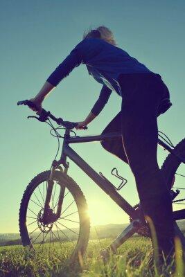 Plakat Dziewczyna na rowerze w zachodzie słońca