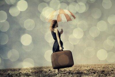 Plakat Dziewczyna Redhead z parasolem i walizka na wietrznym polu