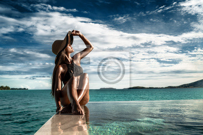 Plakat Elegant luxury black swimsuit swimwear model woman with sun hat on infinity pool resort vacation. Europe holiday hotel for wellness spa, hair removal laser legs and body care.