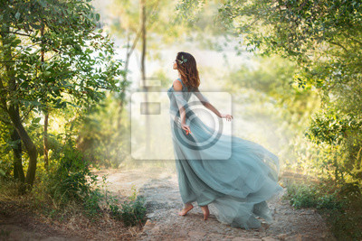 Plakat fairy-tale princess in light summer blue turquoise dress on wide path and walks towards wind, graceful dancing girl in image of flower with flying long hem of dress, nymph of bright green forest