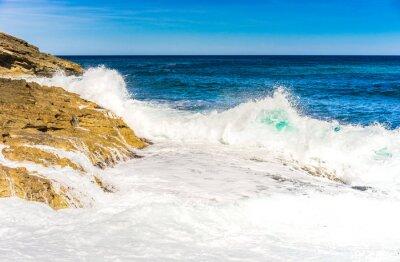 Plakat Fale wody morskiej pianki Skałą Surf