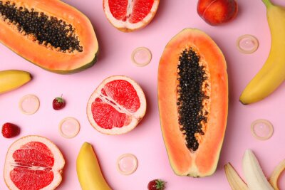Plakat Flat lay composition with condoms and exotic fruits on pink background. Erotic concept