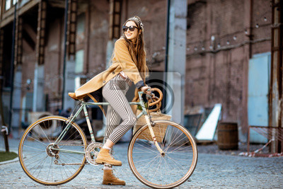 Plakat Full body portrait of a beautiful stylish woman dressed in coat standing with retro bicycle outdoors on the industrial urban background