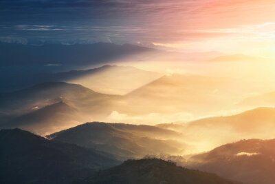 Plakat Gdy noc zmieni się w ciągu dnia. Piękne wzgórza jasno oświetlone podczas wschodu słońca.