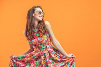 Plakat Girl in floral dress emotionally poses on the orange background.