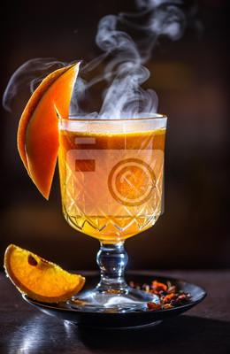 Plakat Gorący pomarańczowy napój z cytryną, arbuzem, cynamonem i innymi przyprawami na ciemnym tle