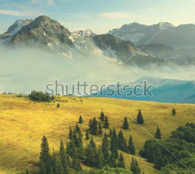 Plakat górski krajobraz, skalista góra w mgle ukośną trawiastą górę