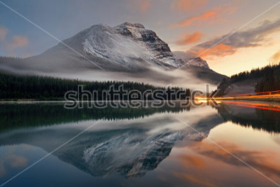 Plakat Górskie jezioro i światłach szlak z refleksji i mgły o zachodzie słońca w Parku Narodowym Banff, Kanada.