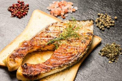 Plakat grillowany filet z łososia na gorąco kromek chleba i przyprawy nad łupkami
