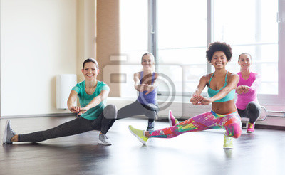 Plakat group of happy women working out in gym