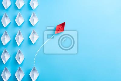 Plakat Grupa białego papieru statek w jeden kierunku i jeden czerwień papieru statku wskazuje w różnym sposobie na błękitnym tle. Biznes dla innowacyjnej koncepcji rozwiązania.