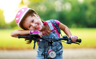 Plakat happy cheerful child girl riding a bike in Park in nature.