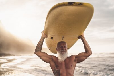 Plakat Happy fit senior having fun surfing at sunset time - Sporty bearded man training with surfboard on the beach - Elderly healthy people lifestyle and extreme sport concep