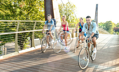 Plakat Happy millenial friends having fun riding bike at city park - Friendship concept with young millennial students biking together on bicycle lane - Bright late afternoon filter with sunshine halo